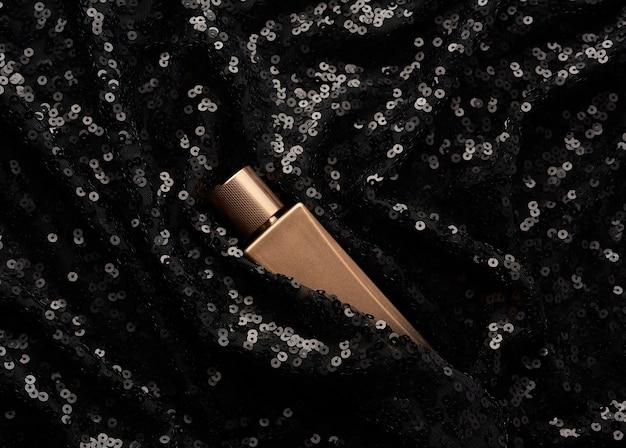 Frasco de vidro dourado de perfume em fundo preto com lantejoulas brilhantes