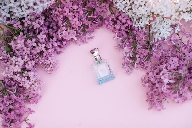 Frasco de vidro e flores lilás no fundo para os termas e a aromaterapia, espaço da cópia para o texto.