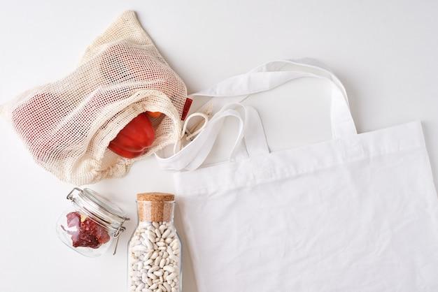 Frasco de vidro e sacola de compras com legumes frescos
