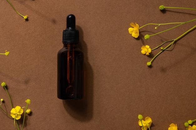 Frasco de vidro marrom de produto cosmético ou óleo sobre pedra e flores silvestres amarelas sobre papel pardo bege ...