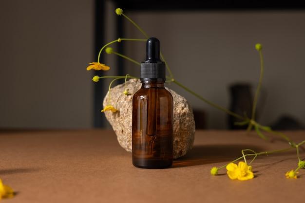 Frasco de vidro marrom de produto cosmético ou óleo sobre pedra e flores silvestres amarelas