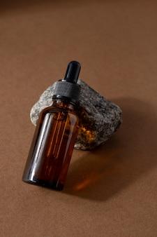 Frasco de vidro marrom de produto cosmético ou óleo sobre pedra no fundo de papel marrom bege natura spa co ...