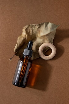 Frasco de vidro marrom de produto cosmético ou óleo sobre pedra sobre fundo de papel marrom bege. conceito de beleza cosmética do spa natura com visão lateral de sombras duras