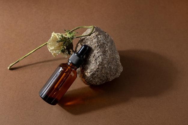 Frasco de vidro marrom de produto cosmético ou óleo sobre pedra sobre fundo de papel marrom bege. natura spa cosmetic beauty conceito com sombras duras vista lateral