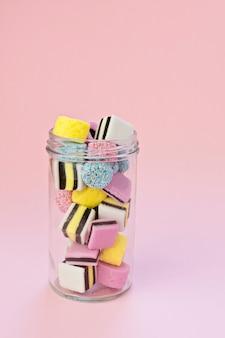 Frasco de vidro pequeno com doces de mascar coloridos