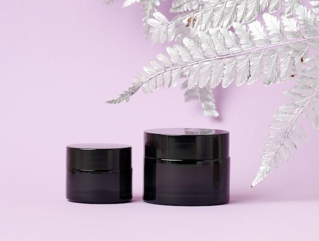 Frasco de vidro preto para cosméticos em um fundo roxo. embalagem para creme, gel, soro, publicidade e promoção de produto, mock up