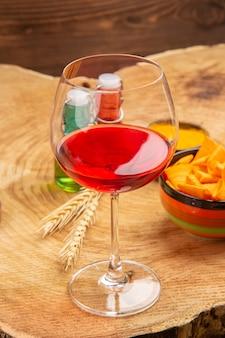 Frasco de vidro vermelho e verde do copo de vinho com vista inferior, chips em uma tigela na superfície marrom