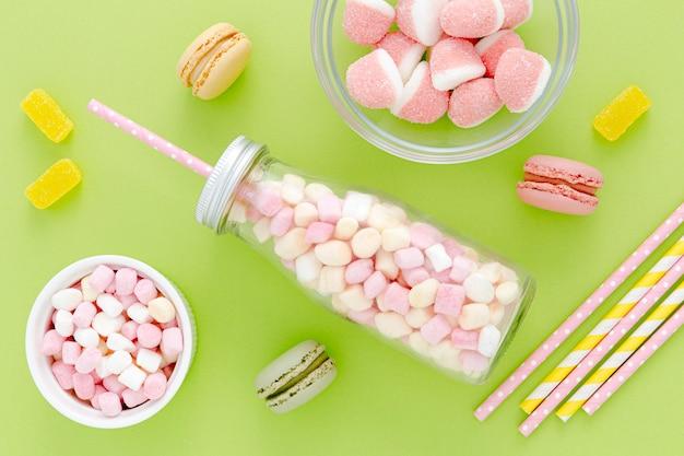 Frasco de vista superior com doces e macarons