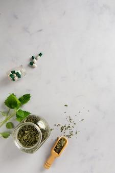Frasco de vista superior com ervas e cápsulas em cima da mesa