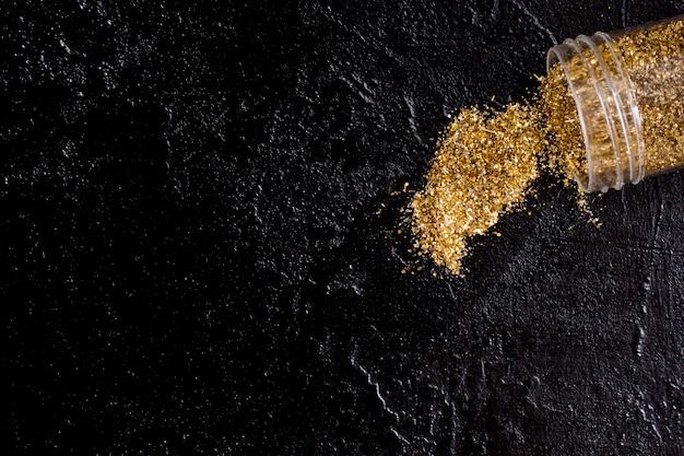 Frasco de vista superior com glitter dourado sobre fundo de ardósia