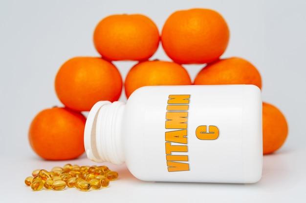 Frasco de vitamina c com cápsula e laranjas espalhadas. isolado em um fundo branco. sistema imunológico saudável.