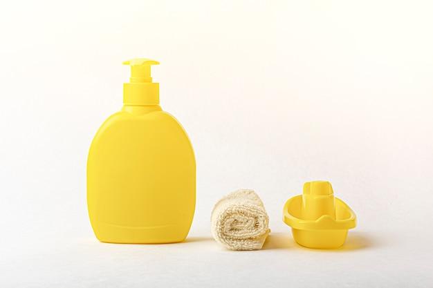 Frasco de xampu amarelo, toalha e brinquedo barco branco.