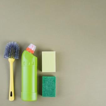 Frasco detergente, escova e esponja em fundo colorido