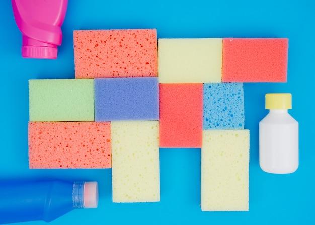 Frasco detergente perto das esponjas multi coloridas sobre fundo azul