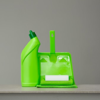 Frasco detergente verde para o toalete, a esponja, a colher e o pano da poeira no cinza.