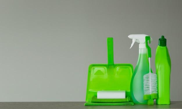 Frasco detergente verde para vaso sanitário, frasco de spray, escova, esponja, colher e pó na superfície cinza.