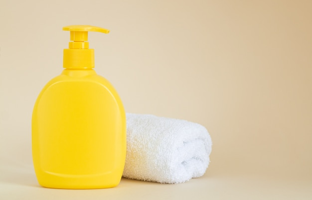Frasco dispensador amarelo sem marca ao lado da toalha branca em bege