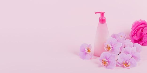 Frasco dispensador de plástico com sabonete cosmético, shampoo ou gel de banho, esponja rosa e flores roxas de orquídea em rosa claro