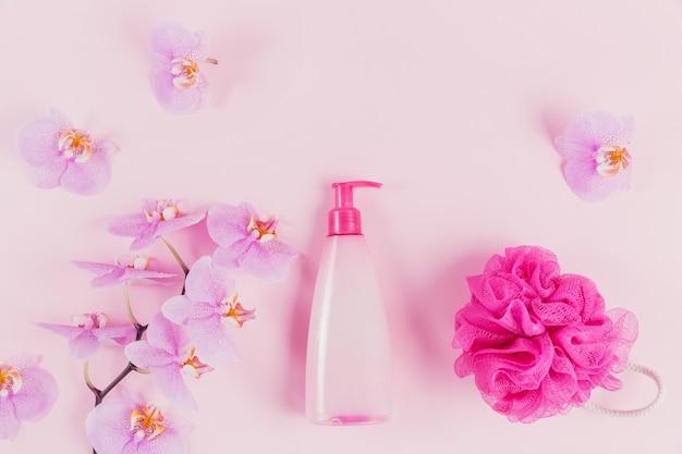 Frasco dispensador de plástico com sabonete cosmético, shampoo ou gel de banho, esponja rosa e flores roxas de orquídea