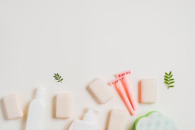 Frasco dispensador; sabão e navalha rosa sobre fundo branco