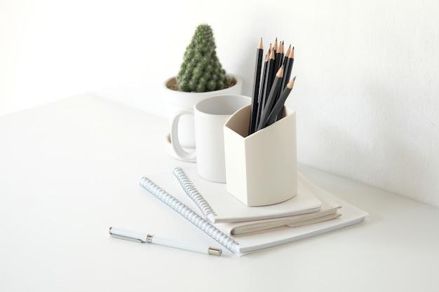 Frasco do lápis e do material de escritório com o cacto na tabela branca.