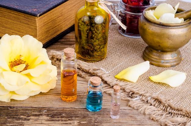 Frasco do petróleo essencial para aromatherapy com as flores cor-de-rosa frescas.