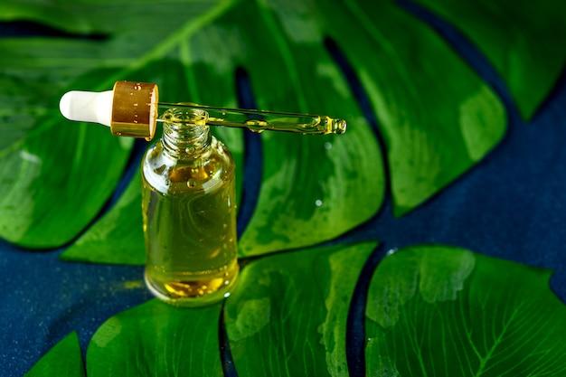 Frasco droper moderno com óleo cosmético amarelo em folhas verdes sobre fundo azul clássico