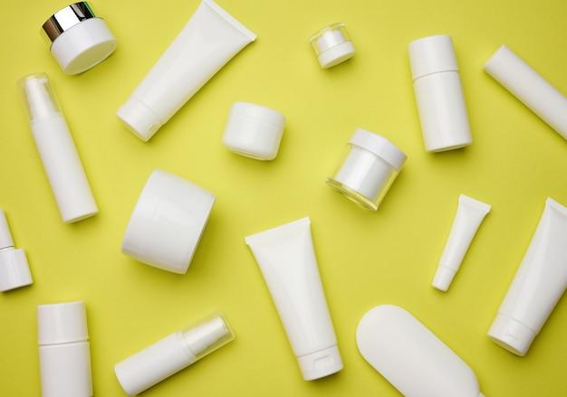 Frasco, garrafa e tubos de plástico brancos vazios para cosméticos em um fundo amarelo. embalagem para creme, gel, soro, publicidade e promoção de produto, vista superior
