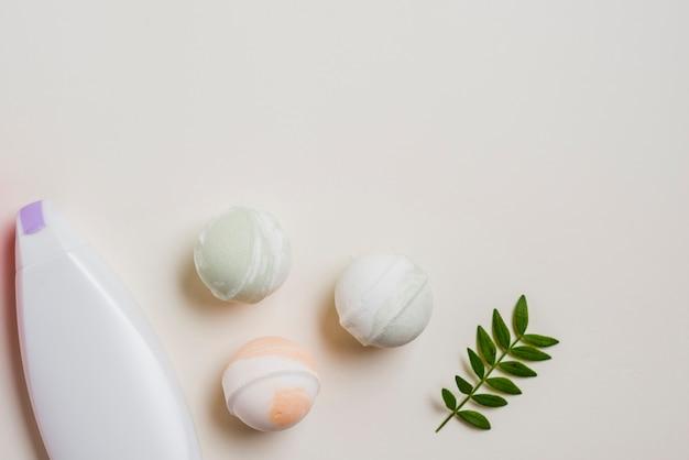 Frasco hidratante; bombas de banho e folhas no fundo branco