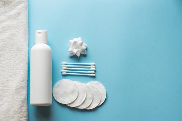 Frasco liso colocado, cotonetes e almofadas de algodão, toalha no fundo azul.