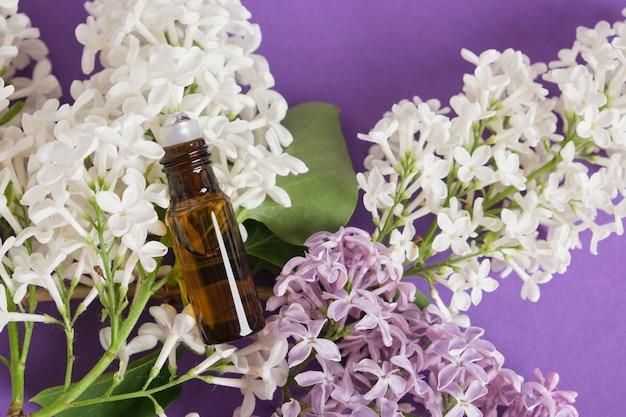 Frasco marrom com aplicador de metal roll-on para perfume artesanal e lilás em um fundo roxo brilhante, óleos e perfume com conceito de perfume de lilás vista superior
