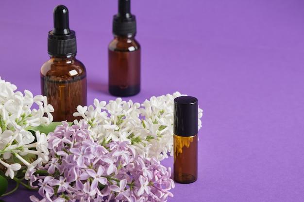 Frasco marrom com aplicador de metal roll-on para perfume artesanal e lilás em um fundo roxo brilhante, óleos e perfume com conceito de perfume de lilás