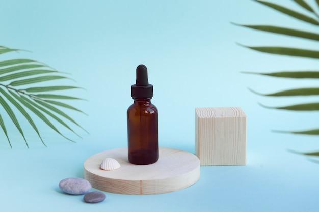 Frasco para produto cosmético em fundo de pódio de madeira de cor azul com folhas de palmeira tropical na