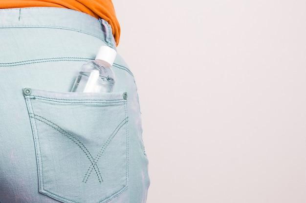 Frasco pequeno com desinfetante em gel no bolso de trás da calça jeans bkue