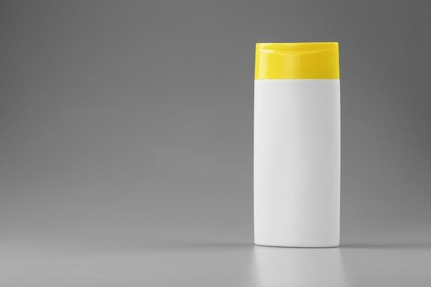 Frasco plástico branco com tampa amarela com gel de shampoo na superfície cinza