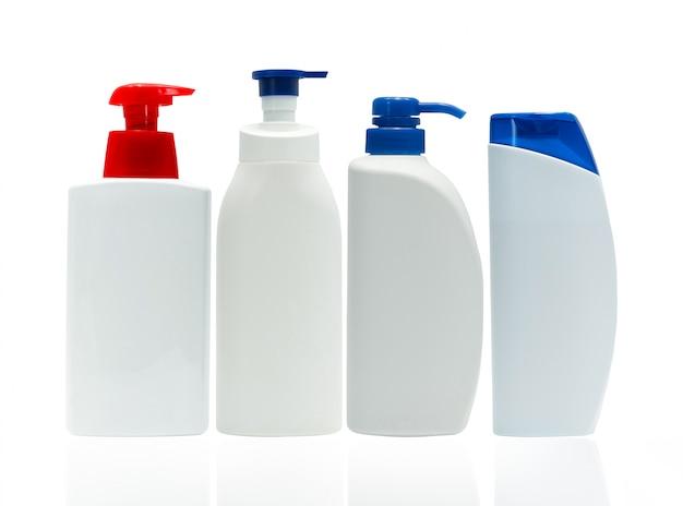 Frasco plástico branco cosmético com o distribuidor vermelho e azul da bomba isolado no fundo branco com etiqueta em branco. conjunto de quatro garrafa de cuidados da pele. loção para o corpo. pacote de frasco cosmético. frasco de xampu.