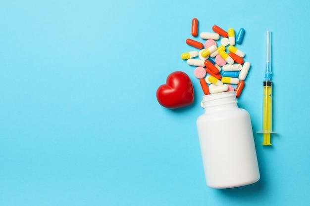 Frasco plástico, pílulas, seringa e coração isolados