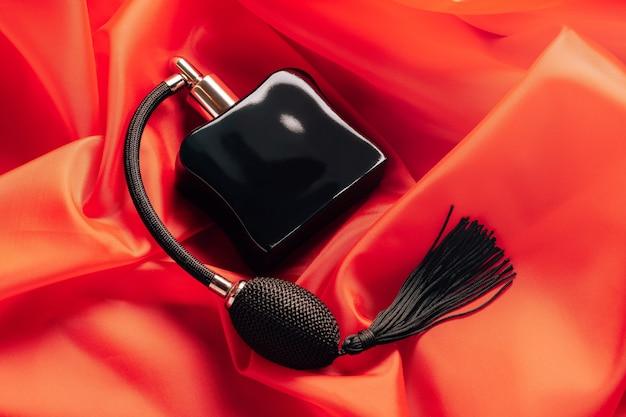 Frasco preto de eau de toilette ou perfume com pompa de spray de borla longa sobre um fundo vermelho de tecido esvoaçante