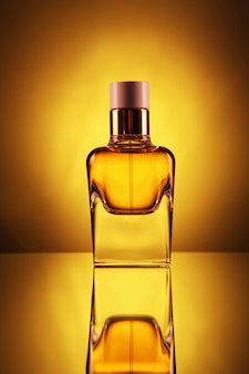 Frasco transparente com perfume da cor do ouro em um amarelo