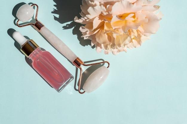 Frasco transparente com soro de beleza, ácido hialurônico e água de rosas sobre fundo azul com rolo massageador de quartzo. conceito luxuoso de tratamento facial e corporal