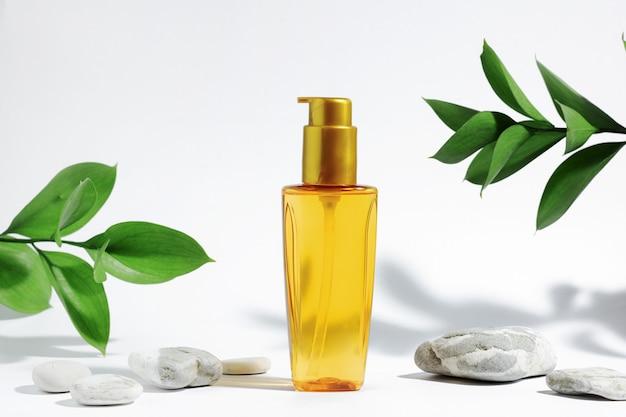 Frasco transparente de óleo amarelo-laranja para proteção solar, bronzeamento ou cabelo