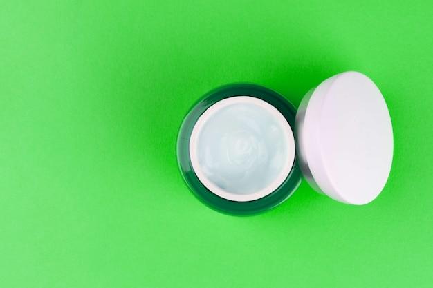 Frasco verde com um gel de creme hialurônico hidratante de dia claro para o rosto em verde