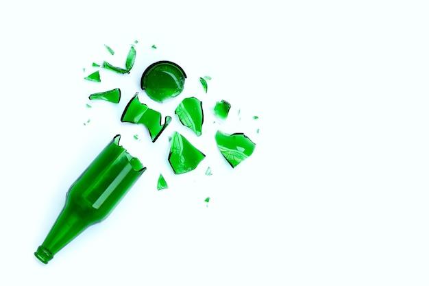 Frasco verde quebrado, cacos de vidro isolados na superfície branca