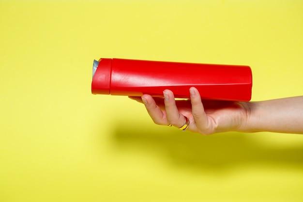 Frasco vermelho nas mãos com shampoo em gel ou sabonete líquido em um fundo amarelo
