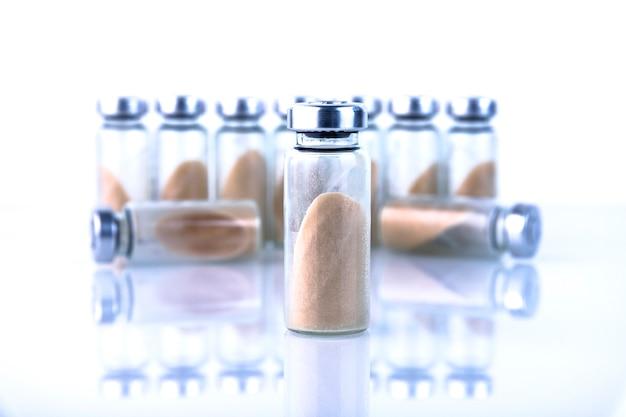 Frascos, ampolas com probiótico seco, bifidobactérias, com pó de probiótico em um fundo branco. copie o espaço.