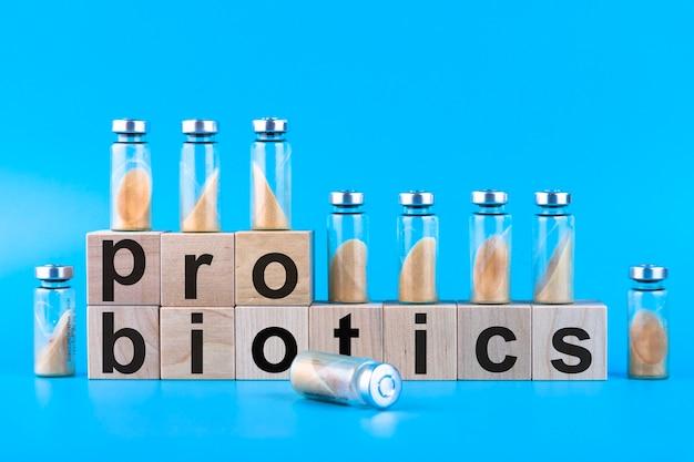 Frascos, ampolas com probiótico seco, bifidobactérias, com pó probiótico em um fundo azul. copie o espaço.
