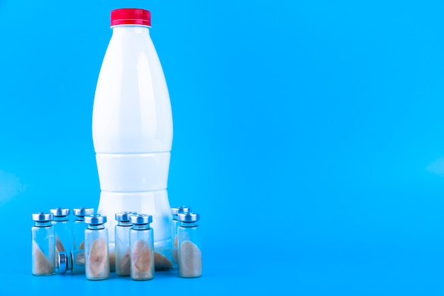 Frascos, ampolas com probiótico seco, bifidobactérias e uma garrafa com leite em um fundo azul. copie o espaço.