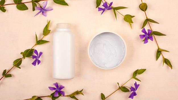 Frascos brancos com cosméticos em um fundo bege com vista superior violeta flores silvestres plano leigos. cuidados com a pele, beleza, limpeza e hidratação da pele