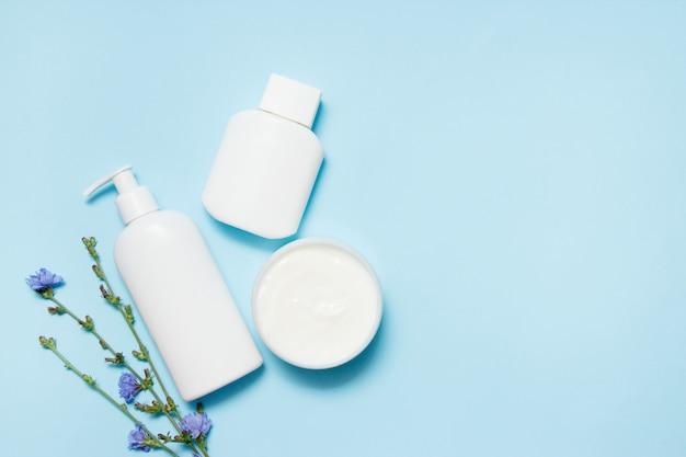 Frascos brancos de cosméticos com flores sobre fundo azul