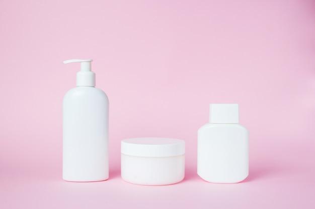 Frascos brancos de cosméticos em rosa